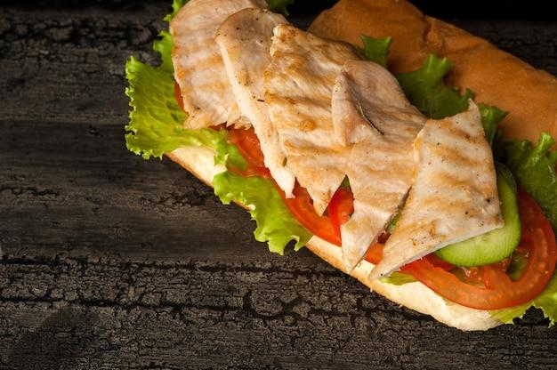 Cheeseburger su una vecchia superficie di legno di hamburger di colore scuro con carne di pollo