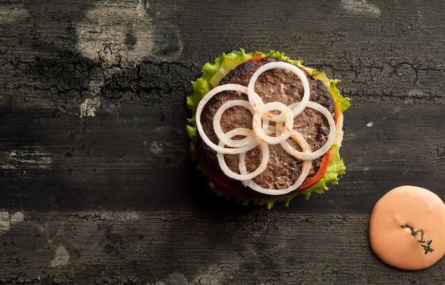 Cheeseburger su una vecchia superficie di legno di hamburger di colore scuro con salsa e ketchup