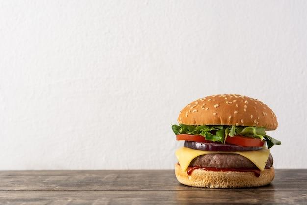 Cheeseburger con carne di manzo, pomodoro, lattuga e cipolla sulla tavola di legno