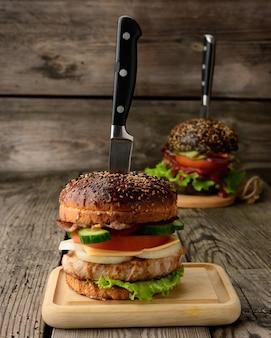 Cheeseburger con panino, carne e verdure su una superficie di legno, fast food e coltello