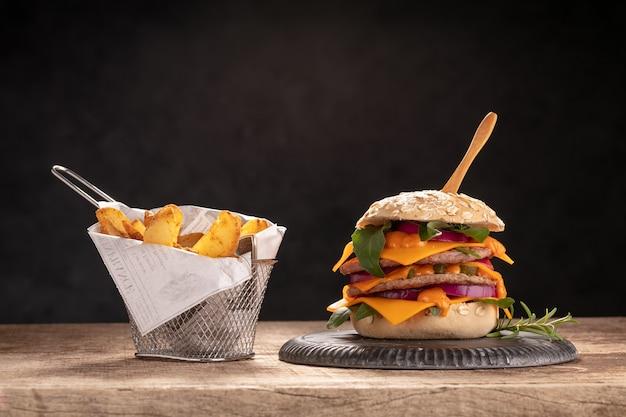 Cheeseburger con patate su un tavolo di legno e una parete scura