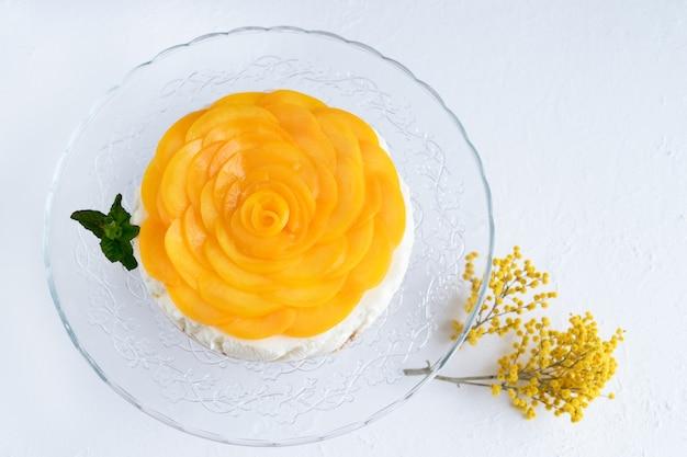 Torta di formaggio decorata con pesche e fiori gialli su sfondo bianco. copia spazio.