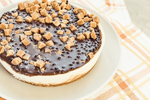 Cheesecake decorata con pezzi di caramello salato. dessert fatto in casa