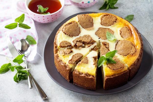 Cheesecake e tazza da tè alla menta cheesecake new york al cioccolato e tazza da tè alla menta su sfondo di cemento