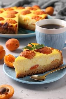Cheesecake con albicocche con un pezzo tagliato, situato su un piatto blu e una tazza di caffè, formato verticale, primo piano