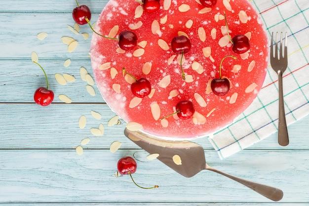 Cheesecake con ciliegie su una superficie chiara, posate vista dall'alto