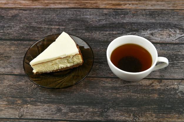 Cheesecake con caffè su un legno scuro. . una cheesecake accanto ad essa su un legno marrone. tazza retrò. caffè in una caffetteria, copia.