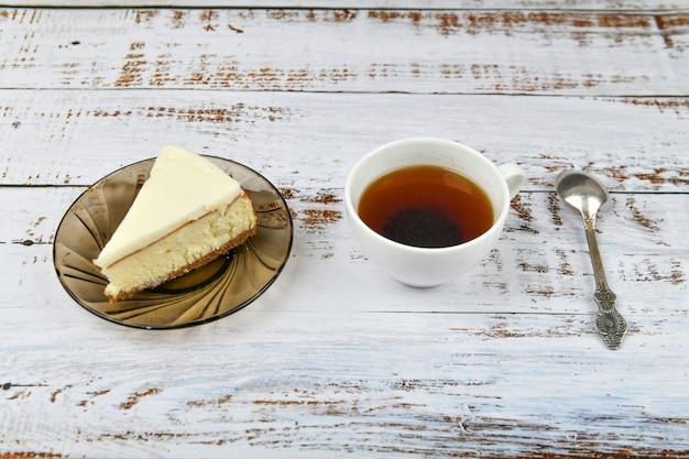 Cheesecake con caffè su un legno chiaro. caffè in una caffetteria, copia. cheesecake di new york su una luce concreta, vista dall'alto. cheesecake classica e una tazza di caffè.