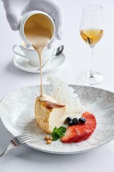 Cheesecake con fragole fresche e mirtilli sulla piastra bianca e il caffè latte sono sul tavolo nella caffetteria e un bicchiere di cognac
