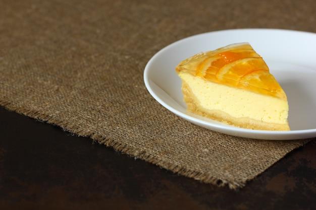 Cheesecake con arance su un piatto bianco e tovaglia di tela da imballaggio.