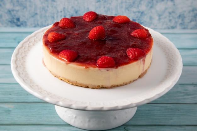 Cheesecake con topping di salsa di fragole su supporto bianco con sfondo blu.