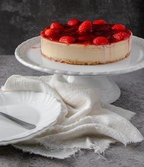 Cheesecake con topping di salsa di fragole su supporto bianco con fondo grigio.