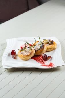 Torte di formaggio decorate con zucchero a velo, ramo di rosmarino e uva con marmellata di frutti di bosco su un piatto bianco. deliziosa colazione con ricotta.