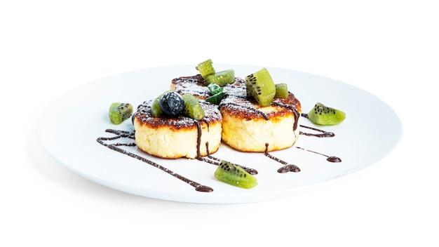 Torte di formaggio con frutti di bosco isolati su bianco. frittelle di formaggio isolate.