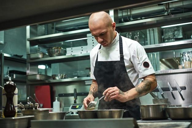 Chef in grembiule nero e con diversi tatuaggi sulle braccia che cucinano un piatto nella cucina del suo ristorante