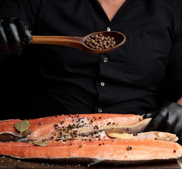 Lo chef in abiti neri e guanti in lattice nero versa pimento su una carcassa affettata di pesce salmone fresco
