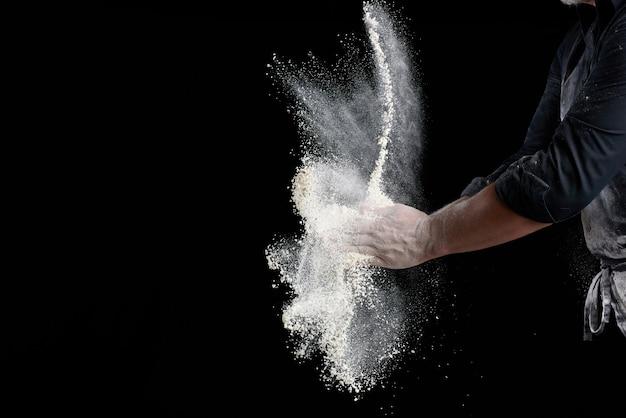 Lo chef in uniforme nera spruzza la farina di grano bianco in diverse direzioni, il prodotto disperde polvere, sfondo nero, copia spazio