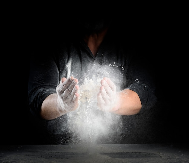 Lo chef in uniforme nera spruzza farina di grano bianco in direzioni diverse, il prodotto sparge la polvere, sfondo nero