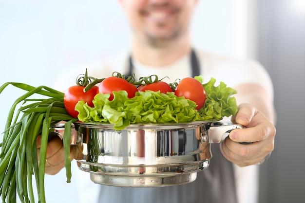 Chef blogger che tiene casseruola di verdure