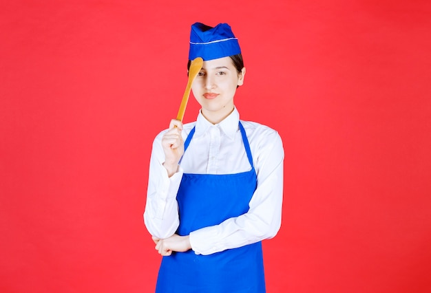 Chef in grembiule blu che tiene un cucchiaio di legno e che sembra premuroso.