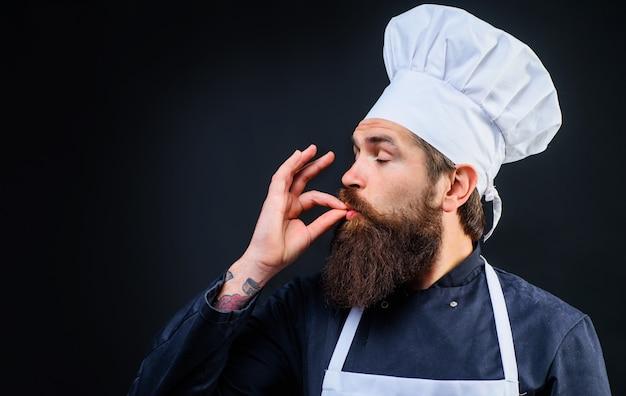 Chef, cuoco, fornaio gesticolano in modo eccellente. lo chef professionista in uniforme mostra il gesto perfetto segno gustoso gustare il pasto.