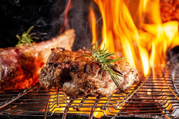 Lo chef cucina patatine fritte di carne, bistecca di manzo su un fuoco aperto in un ristorante