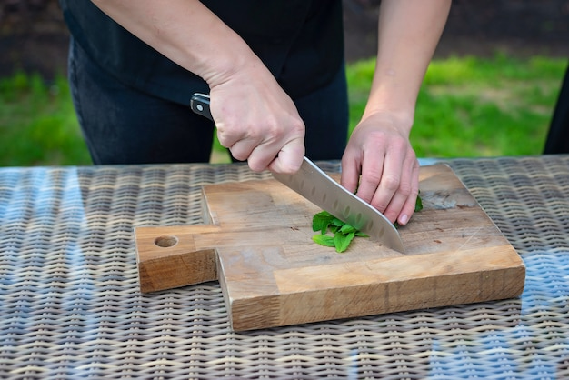 Il cuoco del cuoco unico affetta le verdure su un bordo di legno.