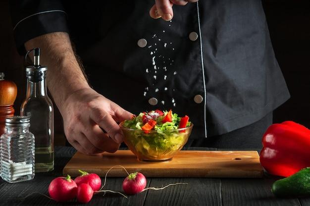Lo chef o il cuoco spruzza insalata di sale di verdure fresche su un tavolo di legno. preparare cibi sani in cucina