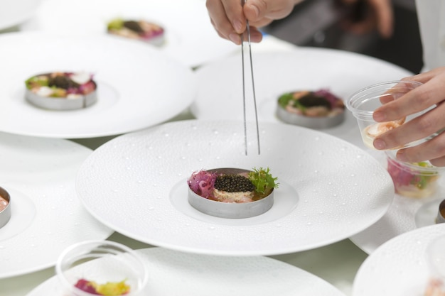 Cuoco unico che cucina caviale e gamberetti nella cucina del ristorante.