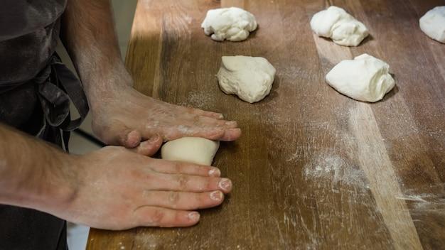Chef che cucina gnocchi di pasta o halusky. preparazione dei pasti presso la cucina professionale. cucina tradizionale