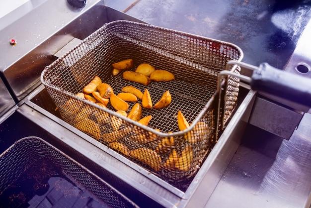 Lo chef che cucina patatine fritte.
