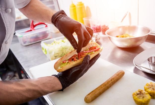 Cuoco unico che cucina hot dog su una griglia. ristorante.
