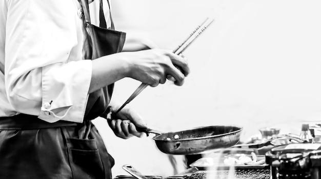 Chef che cucina in una cucina, chef al lavoro, in bianco e nero