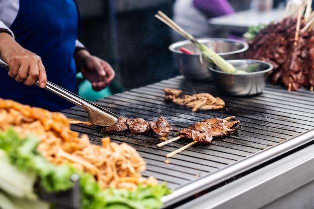 Chef che cucina carne per strada
