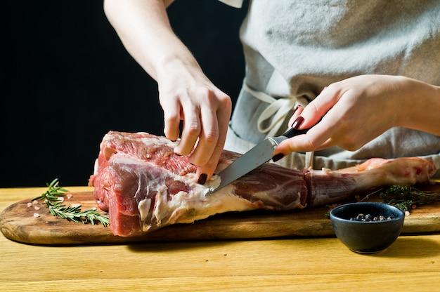 Il cuoco che cucina la gamba della capra cruda su un tagliere di legno. rosmarino, timo, pepe nero.