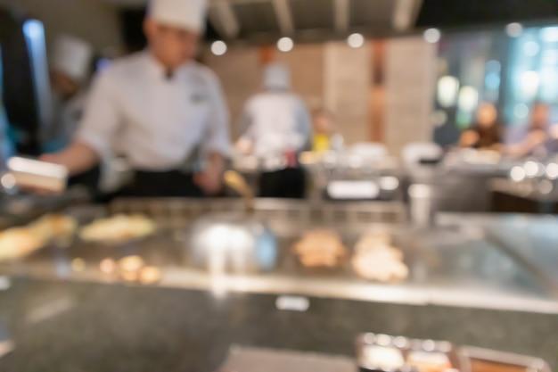 Lo chef che cucina nella cucina del ristorante ha sfocato lo sfondo sfocato