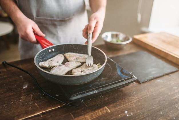 Cuoco unico che cucina il filetto di pesce di branzino su una padella antiaderente