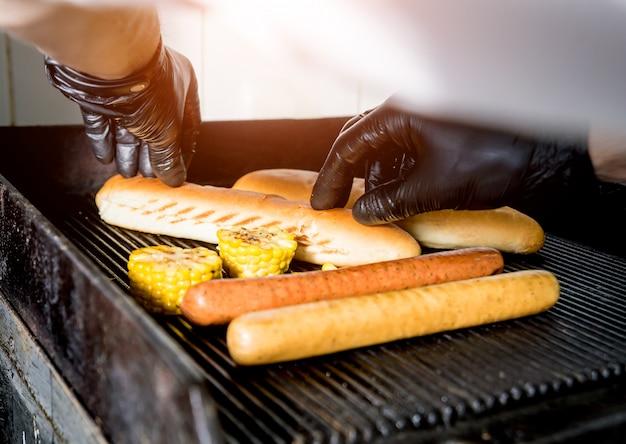 Cuoco unico che cucina due hot dog su una griglia. ristorante.