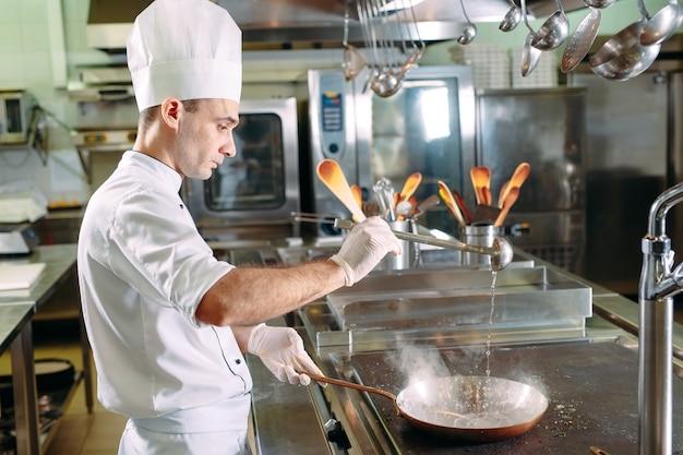 Cuoco unico che cucina le verdure in padella wok. shallow dof.