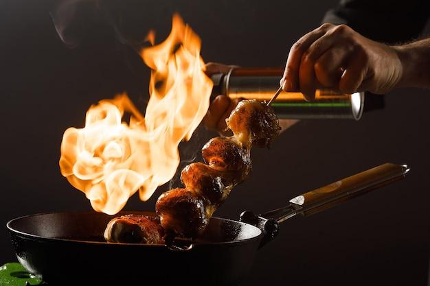 Lo chef cuoce i funghi in una padella con fuoco aperto