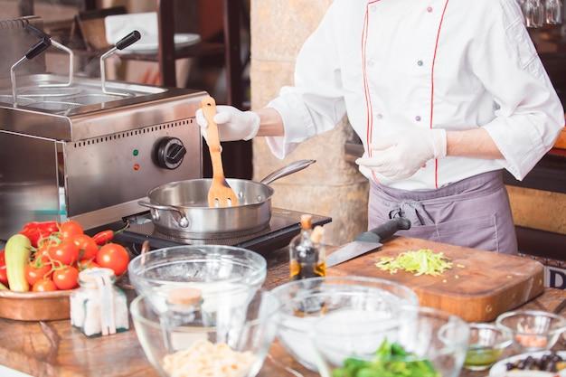 Lo chef cucina gli spaghetti in un ristorante premium.