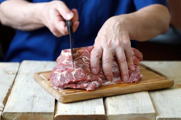 Lo chef taglia la carne cruda sul tagliere