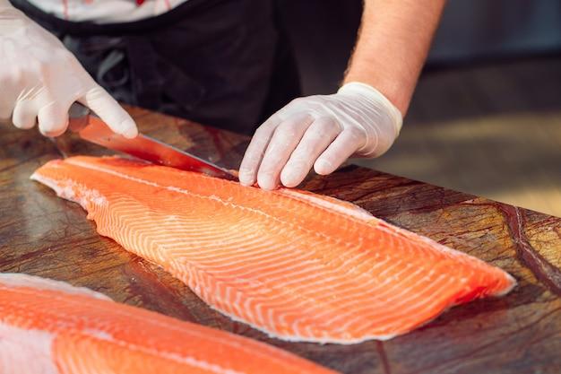 Lo chef taglia il salmone sul tavolo.