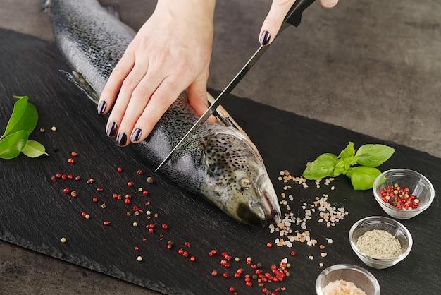 Cuoco unico che taglia il salmone fresco in cucina. lo chef donna taglia il salmone a pezzi