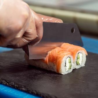 Lo chef taglia il rotolo di sushi leggero philadelphia da vicino