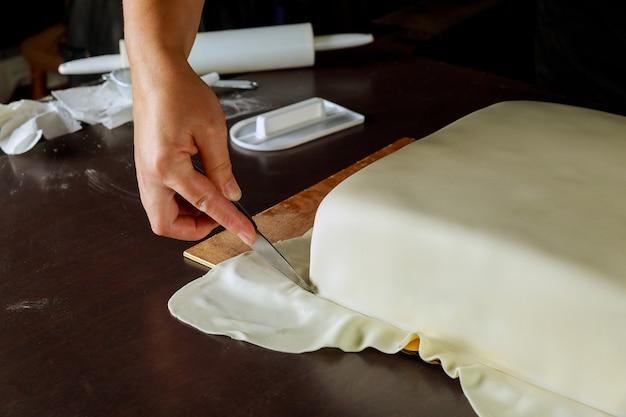 Cuoco unico che taglia fondente bianco sulla torta quadrata. tecnica di decorazione della torta.