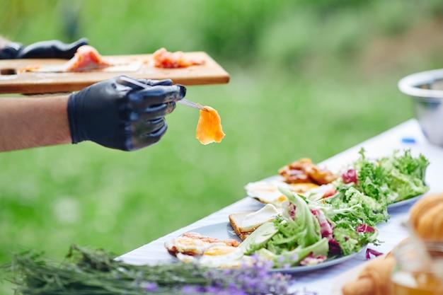 Piatto di rifinitura dello chef con pinzette per salmone