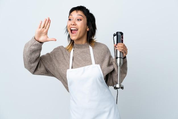 Ragazza del cuoco unico che usando il miscelatore della mano sopra gridare bianco isolato con la bocca spalancata