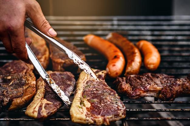 Lo chef bistecche alla griglia con salsicce alla griglia barbecue in fiamme Foto Premium