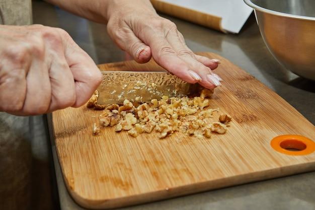 Lo chef macina il dado con il coltello da aggiungere all'insalata. ricetta passo passo.